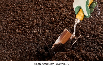 Close up on unidentified hand in rubber and cloth glove using steel trowel to dig into bare soil garden