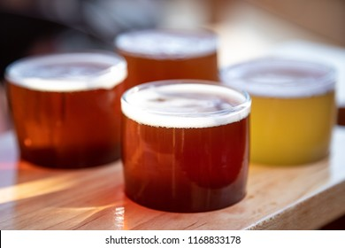 Close up on a variety of craft beers in a wooden carrying tray, as a tasting flight at a brewery