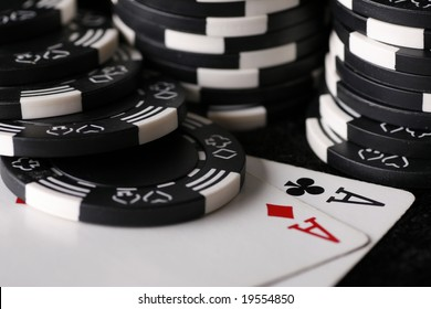 Close up on the very best starting hand in texas holdem poker with casino chips in background.