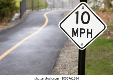 Close up on a white 10 Miles Per Hour sign, along a paved walking and biking trail, with space for text on left