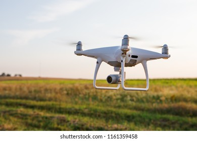 Close up on white drone camera. Drone quadcopter in flight