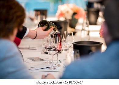 close up on a wine glasses, bottle and red wine being poured