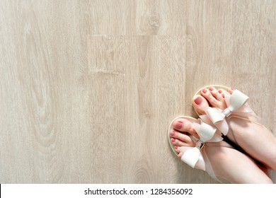 Close Up on Woman is Feet Wearing Bow Shoes Isolated on Wood Floor, Fashionable Accessories. Fashion Flat Shoe (Footwear). Selfie of Feet in Nude Sandals Standing on Wooden Background, Top View.