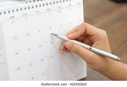 close up on woman hand with pen writing on calender for note or make appointment concept.
