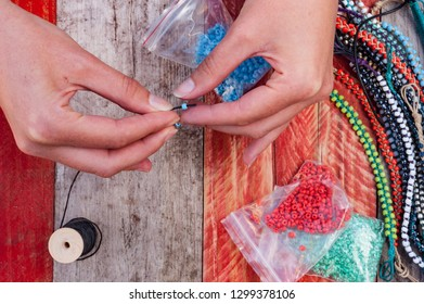 Close up on woman;s hand making colourful bead bracelets on grungy wood background