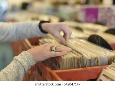 Close up on woman's hands browsing record store