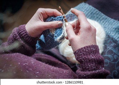 close up on woman's hands crocheting wool
