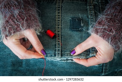 Close up on woman's hands repairing ripped jeans with sewing needle and thread