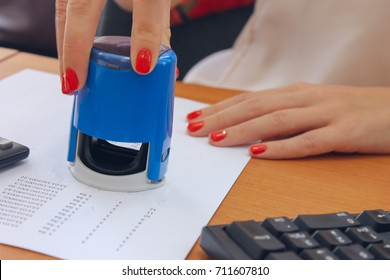 Close up on woman's notary public hand stamping the document. Notary public concept