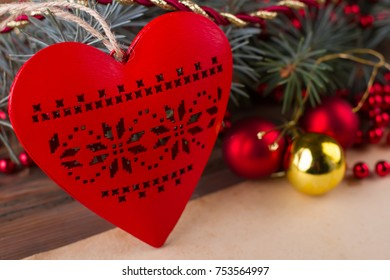 Close up on wooden heart with cut out pattern. Red and yellow ornaments for Christmas tree.