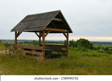 A close up on a wooden hut with a slanted rood and walls made out of boards located at the top of a tall hill and surrounded with various shrubbery and herbs seen on a cloudy sumer day in Poland