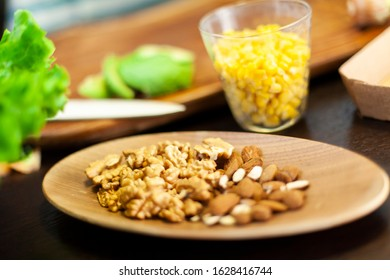 Close up on a wooden plate with shelled almonds and walnuts. Corn and avocado on the background
