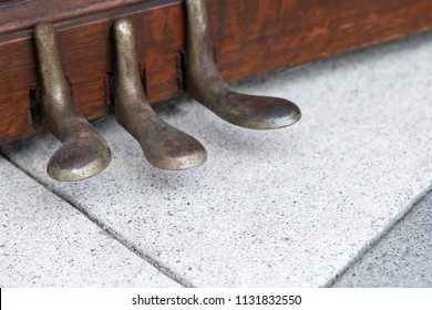 Close up on worn brass foot pedals for soft, damper, and sostenuto, on an upright piano, with space for text on bottom
