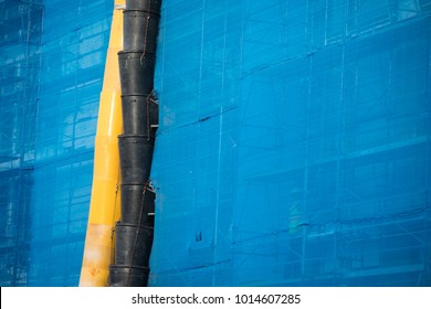Close up on yellow and black plastic garbage chutes on the exterior of an office building, with blue tarps covering scaffolding, at an industrial construction site