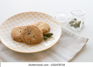 Close up on a Yellow Patterned Plate with Chocolate Chip Cookies and a Glass Jar with Marijuana Buds