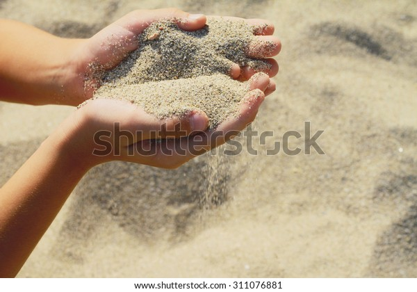 Close up onChilds hands holding sand.summer beach holiday vacation concept