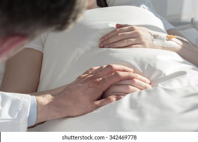 Close up of oncologist holding hand of girl with leukemia