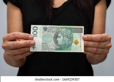 close up of one banknote with a face value of PLN 100 Polish money, zloty held  in the hands of a women on a grey background