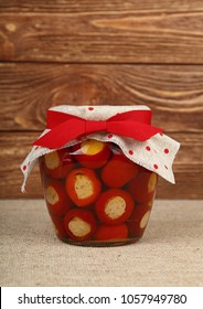 Close up of one glass jar of pickled red hot cherry chili pepperoncini peppers stuffed with soft ricotta cheese with linen canvas lid decoration and red ribbon on brown woodn background, low angle s