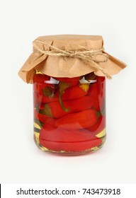 Close up of one glass jar of pickled red hot cherry chili pepperoncini peppers with kraft paper parchment decoration and twine over white background, low angle side view