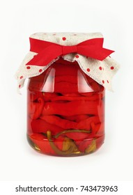 Close up of one glass jar of pickled red hot cherry chili pepperoncini peppers with linen canvas lid decoration and red ribbon over white background, low angle side view
