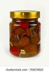 Close up of one glass jar of pickled red and green hot cherry chili pepperoncini peppers with golden lid over white background, low angle side view