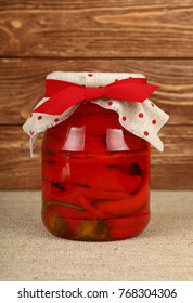 Close up of one glass jar of pickled red hot cherry chili pepperoncini peppers with linen canvas lid decoration and red ribbon over brown wooden background, low angle side view