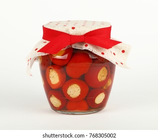 Close up of one glass jar of pickled red hot cherry chili pepperoncini peppers stuffed with soft ricotta cheese, linen canvas lid decoration and red ribbon on white background, low angle side view