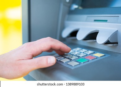 Close up of one hand entering pin at an ATM