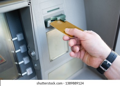Close up of one hand inserting ATM credit card into bank machine to withdraw money