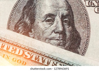 Close up of one hundred dollars and the portrait of Benjamin Franklin on the USA money banknote with a sunlight. Financial, business, investment and economical concept. Top view.