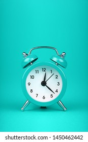 Close up one small teal blue metal twin bell retro alarm clock over aqua turquoise paper background with copy space, low angle front view