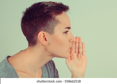Close up One woman telling a secret holding hand near mouth secrecy gesture isolated green background wall. Horizontal image studio shot