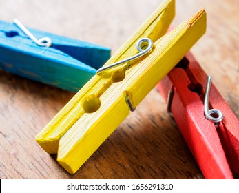 A close up of one yellow painted wooden washing line clothes peg resting diagonally on one red and one blue clothes peg.