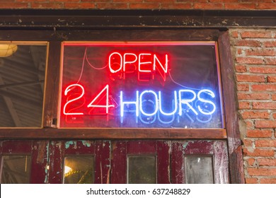 close up open 24 hours sign on the old crimson door with brick wall