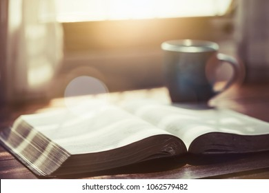 close up of open bible with acup of coffee for morning devotion on wooden table with window light
