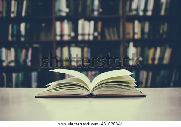 ビンテージフィルタのぼかした背景に、机と本棚の開いた本の接写