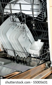 close up of an open dishwasher with plates
