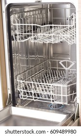 Close up of open empty dishwasher in kitchen