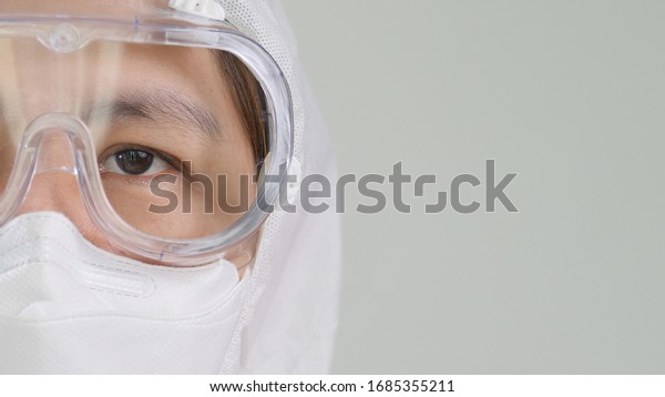 Close up open eye of Asian doctor in protective hazmat PPE suit wearing face mask and eyeglasses with copy space