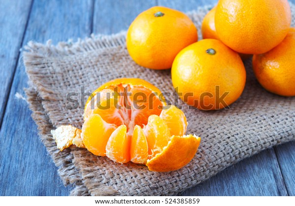 Close up of open fresh clementines on a wooden table.