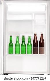 Close up of an open fridge full of beer bottless