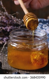 Close up of open glass jar of liquid honey with honeycomb inside, flowing honey from honey dipper, fresh blueberries and bunch of dry lavender over old wooden table with blue rag. Dark rustic style