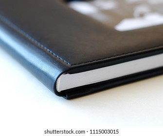 Close up opened book page. Black cover, white background. Photobook with leather cover