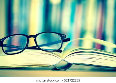 Close up opened book page and  reading eyeglasses with  blurry bookshelf background for education and publication concept , extremely DOF with vintage retro color tone