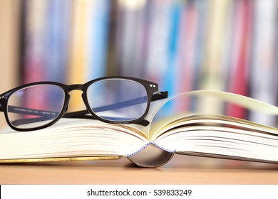 Close up opened book page and  reading eyeglasses with  blurry bookshelf background for education and publication concept , extremely shallow DOF