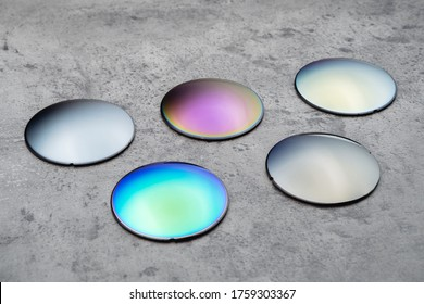 Close up of optical lenses for sunglasses with different color. Production and adjust of new eyeglasses lens in optics. Eyesight concept