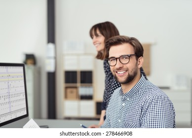 Close up Optimistic Young Bearded Businessman with Eyeglasses Sitting at his Worktable and Smiling at the Camera with his Female Co-worker Behind Him.