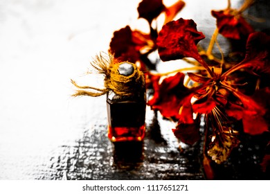 Close up of orange colored flowers of flame tree or gulmohor or goolmohor on a wooden surface with its essence in a transparent bottle.