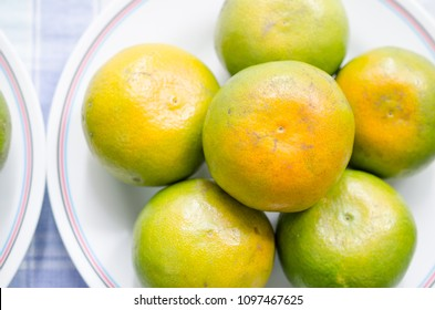close up orange fruit on white plate.